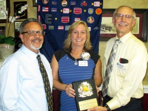 Youth Guidance Mentoring Academy Director Felix L. Cruz and Executive Director Doug Borrie present an appreciation plaque to Jenny Frederick, president of Exchange Club of Indian River